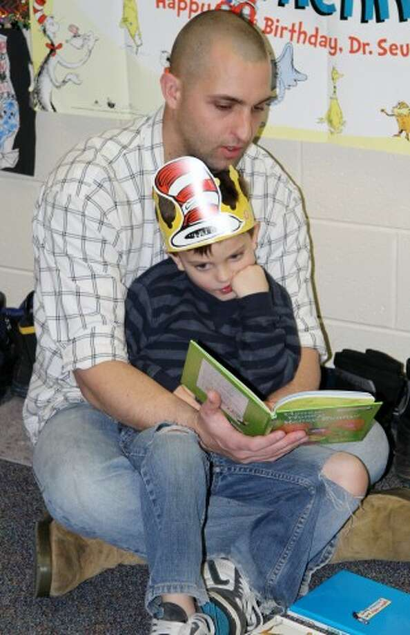 SEUSS STORIES: Matt Cantrell reads a Dr. Seuss book to his son, Logan, during a Read Across America Day celebration in Mrs. Courser's class at Mecosta Elementary School. This year marked the 13th time Courser has held such an event for her students.