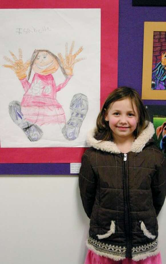 SELF PORTRAIT: Isabelle Johnson, a first grader at Brookside Elementary School, was pleased to see her self-portrait hanging up as part of Art Attack. She created the piece in an Artworks after school class. The first step was to trace her shoes and hands, fill in the details and then draw in the rest of her body.