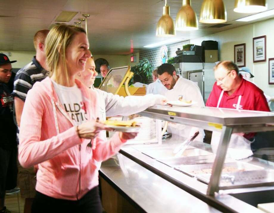 "BULLDOG BREAKFAST: Ferris State University student Kasandra Liske (bottom left) picks up her breakfast at ""Pancakes with the President"" on Monday. (Pioneer photos/Lauren Fitch"