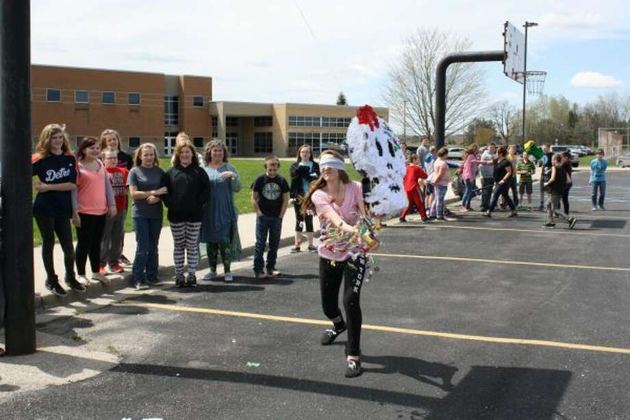 ON TARGET: Morley Stanwood sixth-grader Paig Slocum whacked the sugar skull pinata for the last time, spilling the candy out for her classmates to enjoy. (Pioneer photo/Candy Allan)