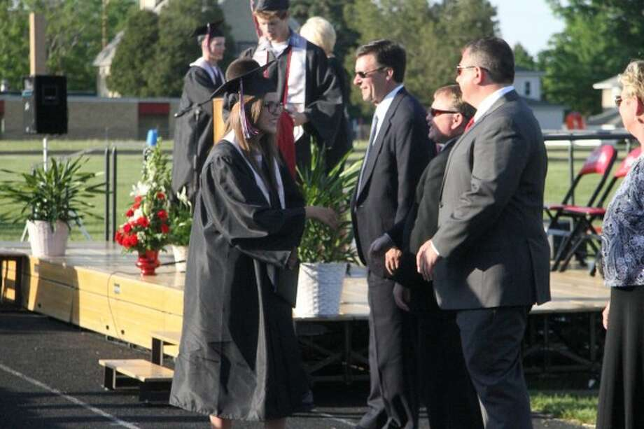 CONGRATS: Hannah Cowsert shakes the hands of members of the Reed City Board of Education after receiving her diploma. (Pioneer photo/Emily Grove-Davis)