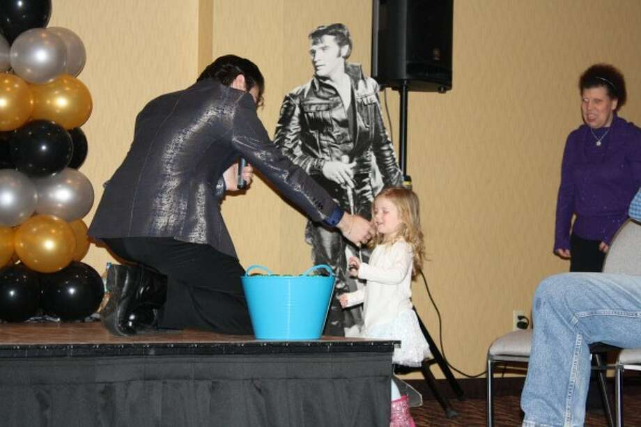 """LITTLEST FAN: Elvis tribute artist Jake Slater noticed two-and-a-half year old Lachlyn Humphreys, of Big Rapids, dancing at the side of the stage and called her over during a song. Later, while singing """"(Let Me Be Your) Teddy Bear"""" Humphreys was one of the audience members to receive a stuffed bear. (Pioneer photo/Candy Allan)"""