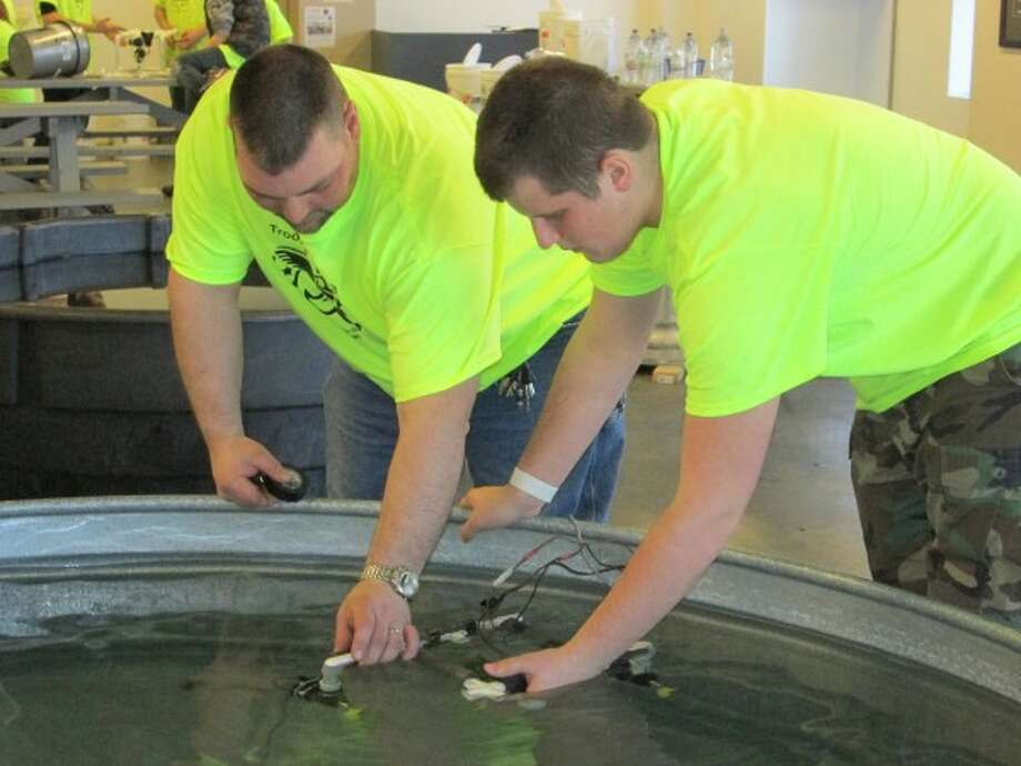 WORKING TOGETHER: Scoutmaster Mike Newhall (left) helps Senior Patrol Leader Dryden Hauger during an underwater robotics class in April at the U.S.S. Silversides museum in Muskegon. (Courtesy photo)