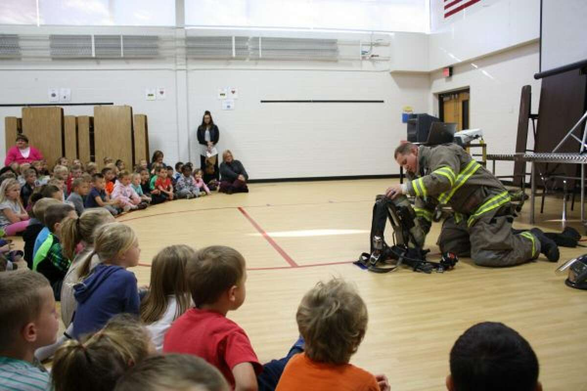 Big Rapids Department of Public Safety-Fire Division firefighter Sean Wethington turns on his oxygen tank before showing Riverview Elementary students how firefighters put it on by flipping it over their heads. (Pioneer photo/Candy Allan)
