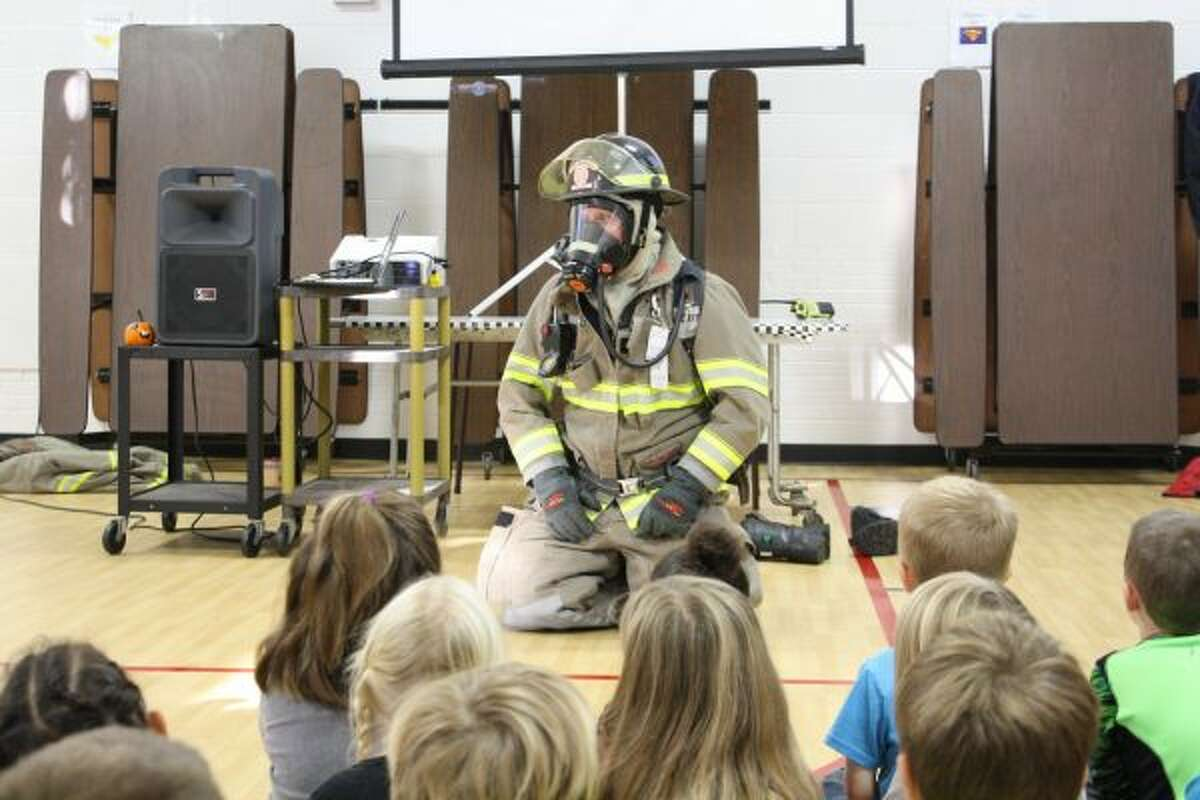 Big Rapids firefighter Sean Wethington sits in front of Riverview Elementary students so they can hear what his oxygen tank sounds like while it's operating and what his voice sounds like through the microphone. (Pioneer photo/Candy Allan)
