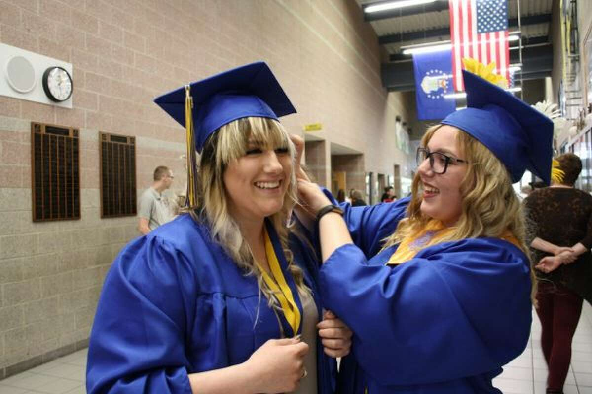 M'Kena Nelson (left) laughs while Lilly Nunn (right) helps her with her mortarboard before graduation on Sunday. (Pioneer photo/Candy Allan)