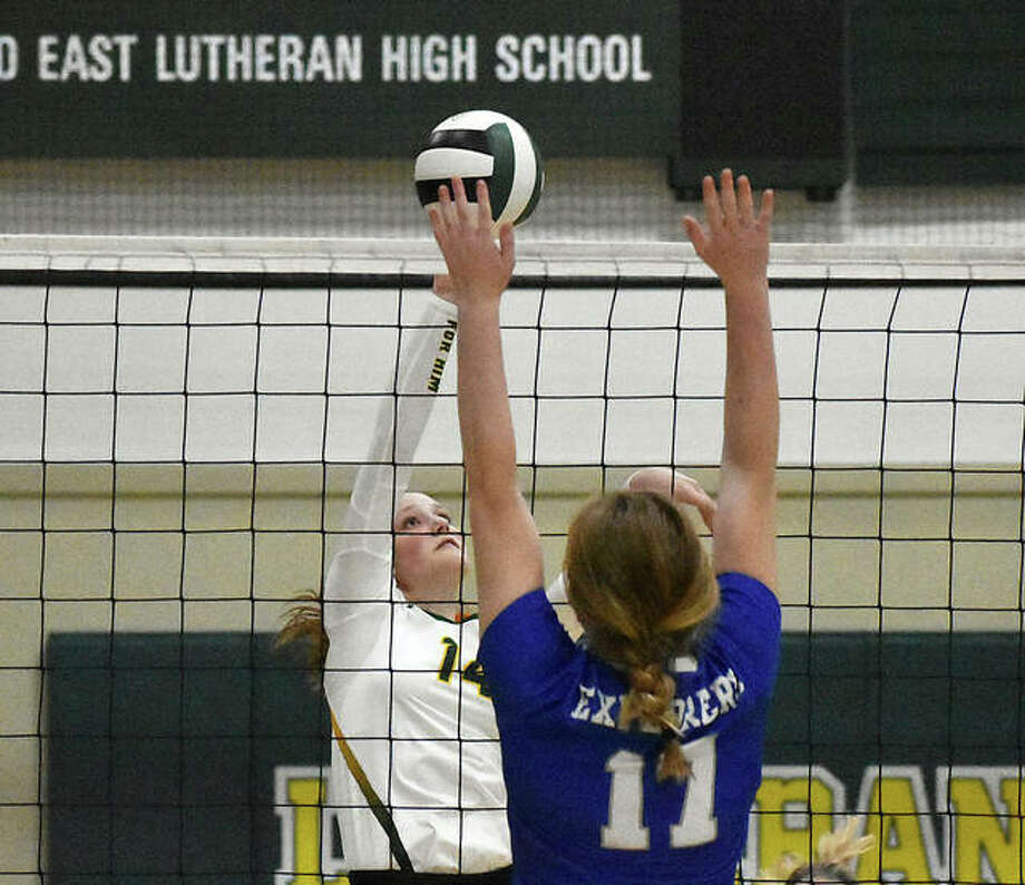 Metro-East Lutheran's Marissa Lowe tries to tip a shot past the Marquette blocker in the first game. Photo: Matt Kamp|The Intelligencer