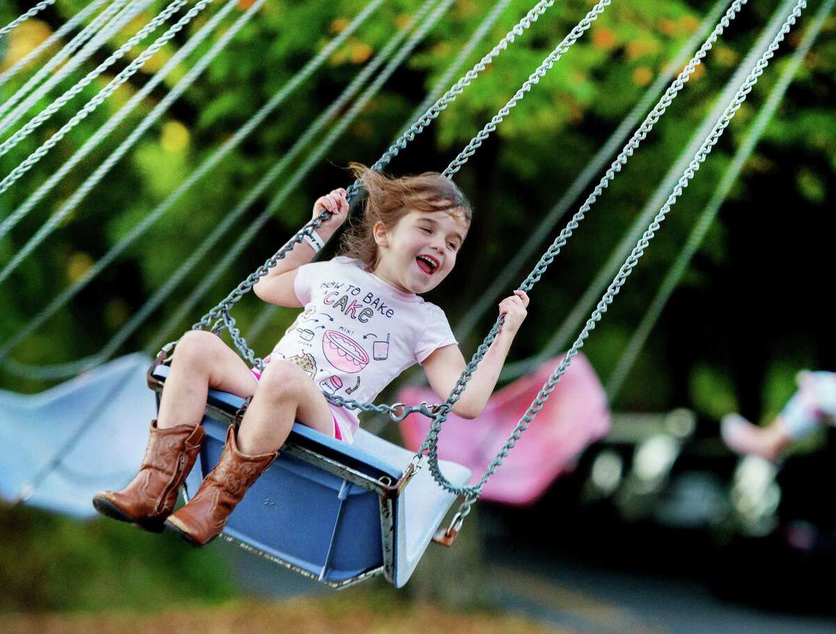 Sadie Eskenazi rides the swing at the Miller-Driscoll PTA carnival on Sept. 27.