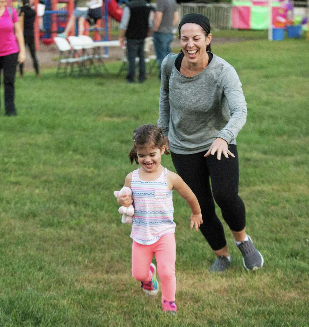 Three-year-old Lyla plays tag with her mother, Kelly, at the Miller-Driscoll PTA carnival.