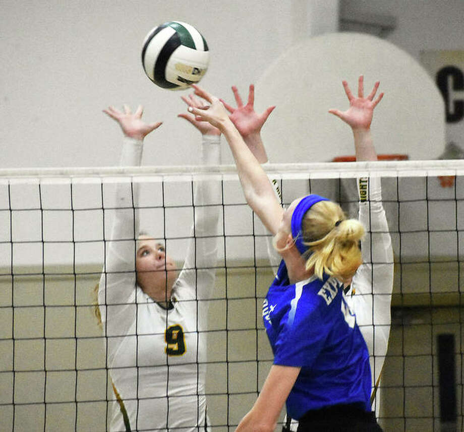 Marquette Catholic's Emma Menke tips over the double block of Metro-East Lutheran's Caitlin Reynolds (left) and a teammate during a Prairie State Conference girls volleyball match Wednesday night at Hooks Gym in Edwardsville. Photo: Matt Kamp / Hearst Illinois