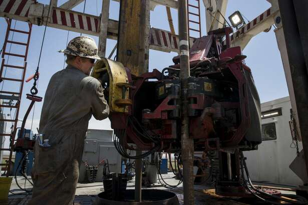 """Caleb Adair, a floorhand from Booneville, Ark., builds stands on a drilling rig near Malaga, N.M. The task consists of joining together three sections of pipe, called """"joints."""""""