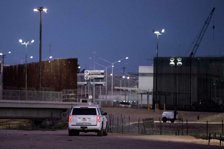 A Border Patrol agent sits near a Calexico port of entry, where a section of the border fence that is painted black is to the right, on Aug. 22 in Calexico, Calif. The standard color of the border fence is seen to the left. Photo: Washington Post Photo By Carolyn Van Houten / The Washington Post