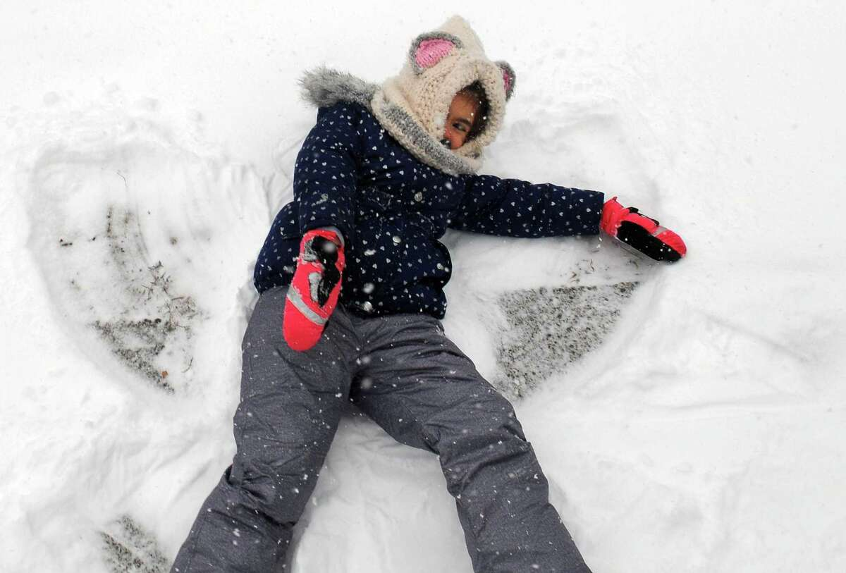 Abree Garriga, 5, makes a snow angel in front of her home along Bunkingham Ave in Milford, Conn., on Tuesday, Feb. 12, 2019.