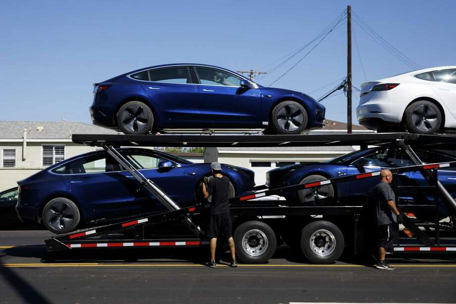 Tesla Model 3 electric vehicles are unloaded from a car carrier at the company's delivery center in Marina Del Rey, Calif., on Sept. 29, 2018. Photo: Bloomberg Photo By Patrick T. Fallon. / © 2018 Bloomberg Finance LP