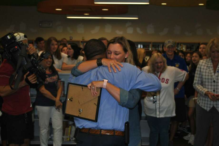 Spring Forest Middle School parent Kara Irvine and principal Raymorris Barnes share an emotional moment after Barnes was presented a Red Apple Award in recognition of his service to the school. Photo: Courtesy Photo