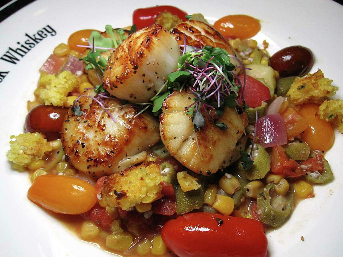 Sea scallops come with grilled corn, okra succotash, tomatoes and cornbread at Maverick Whiskey.
