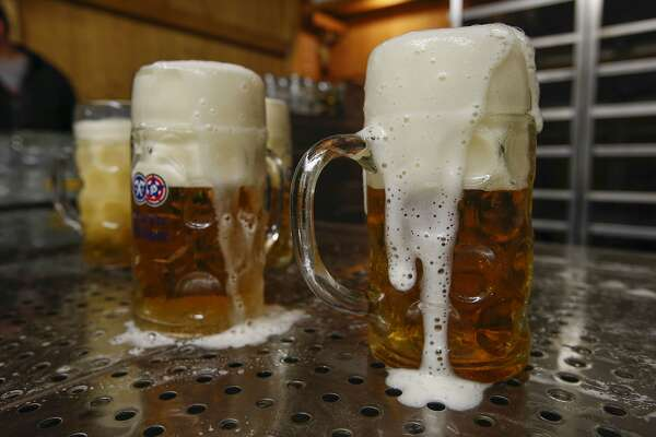 Pints of frothy Hacker-Pschorr beer sit on a bar drainage tray inside the Paulaner Brauerei GmbH 'Hackerzelt' beer tent at the Oktoberfest in Munich, Germany, on Thursday, Sept. 26, 2019. Almost 8 million liters, enough to fill more than three Olympic-sized swimming pools, flow from 28,000-liter tanks and into the bellies of roughly 6 million revelers at Munich's annual Oktoberfest. Photographer: Michaela Handrek-Rehle/Bloomberg