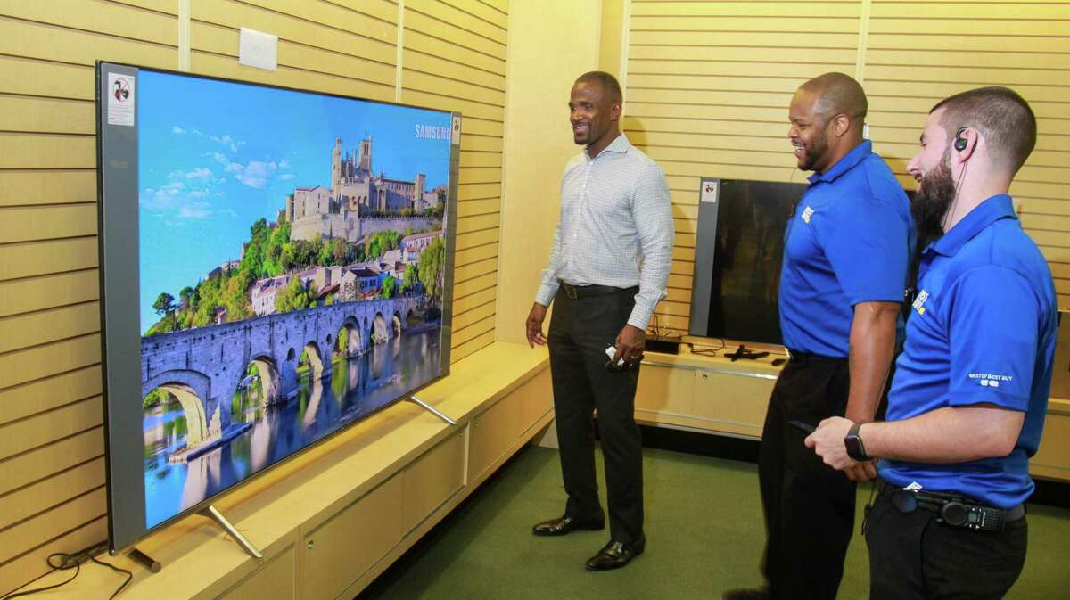 Andre Johnson, from left, gets help with a TV he just purchased from manager Desmond Mays and Cameron Higgins of Best Buy, at the first Best Buy Outlet store. The store offers open-box appliances, TVs and electronics at a discount of up to 60 percent, opened recently on Tomball Pkwy. September 27, 2019.