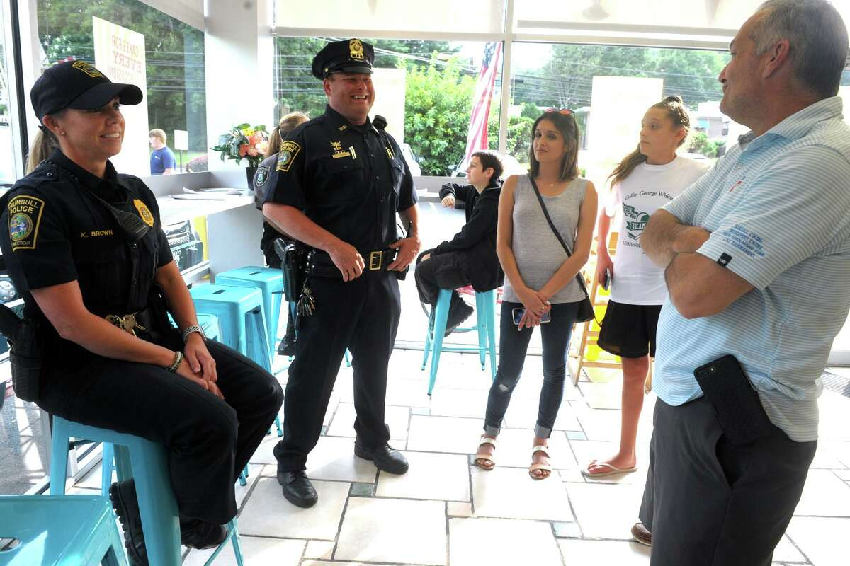 Members of the Trumbull Police Department, including Chief Michael Lombardo, right, visited Sunny Daes ice cream shop during the Cops and Cones event in Trumbull, Conn. Aug. 16, 2019.