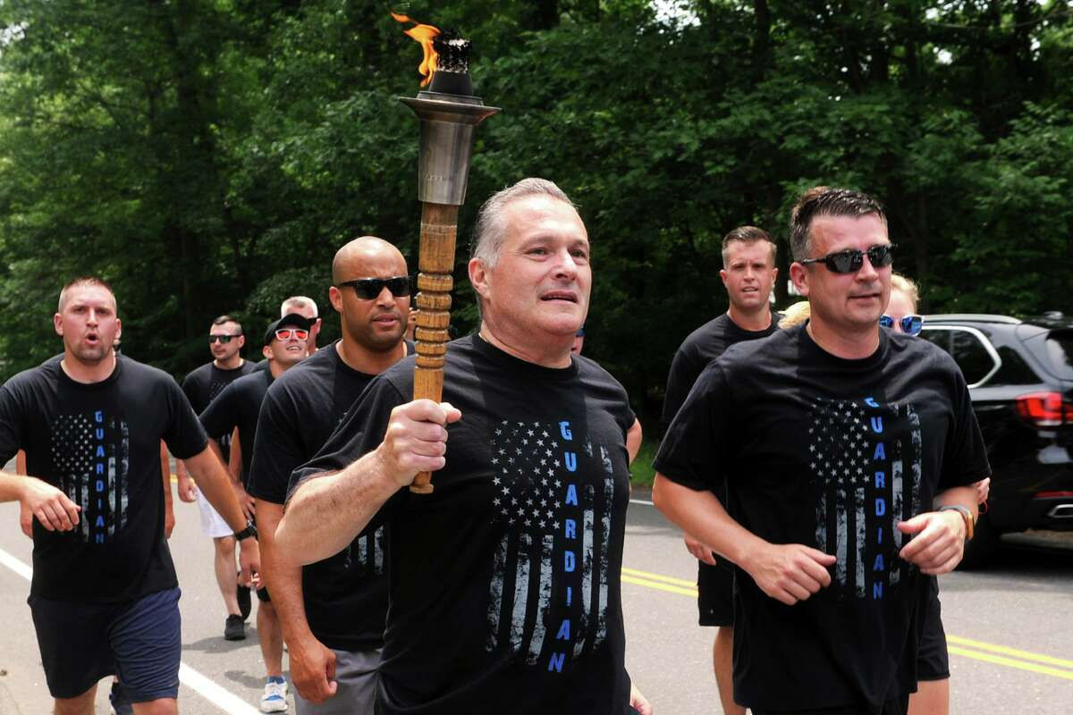Trumbull Police Chief Michael Lombardo carries the torch in the Law Enforcement Torch Run for Special Olympics, seen here in Trumbull, Conn. June 8, 2018. The three-day run by police officers covered several routes through over 100 cities and towns in the state, and culminated at the opening ceremonies Friday for Connecticut Special Olympics, which take place this weekend at Southern Connecticut State University.