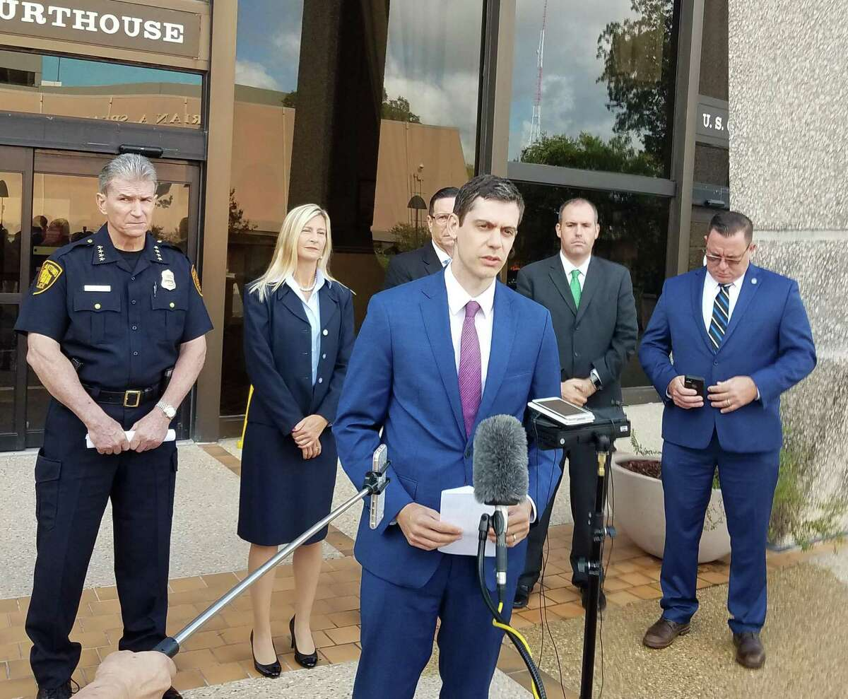 John F. Bash, U.S. Attorney for the Western District of Texas, addresses the media Oct. 3, 2019, in front of the John S. Wood Federal Courthouse in San Antonio after Alaa Mohammed Allawi, the leader of an opioid trafficking ring that started in San Antonio, was sentenced to 30 years without parole. Monday, another one of Allawi's ring members, Trevor Alan Robinson, was sentenced to 10 years for his role in the ring. Standing behind Bash, left to right, are: San Antonio Police Chief William McManus; Assistant U.S. Attorney Sarah Wannarka, who prosecuted the case; F. Dante Sorianello, San Antonio's DEA assistant special agent in charge in San Antonio (wearing glasses); U.S. Postal Inspection Service Assistant Inspector in Charge Nikolas Charette, Houston Division (green tie); and Charles Humenansky, special agent in charge of the Naval Criminal Investigative Service, Carolinas Field Office (Camp Lejeune).