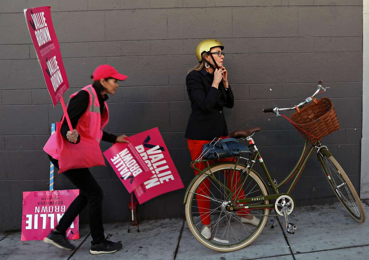 Supervisor Vallie Brown (right), candidate for D5, gets ready to leave on her bike after campaigning on McAllister at Divisidero bus stop on Wednesday, Oct. 2, 2019, in San Francisco, Calif. At left is volunteer Leela Gill.
