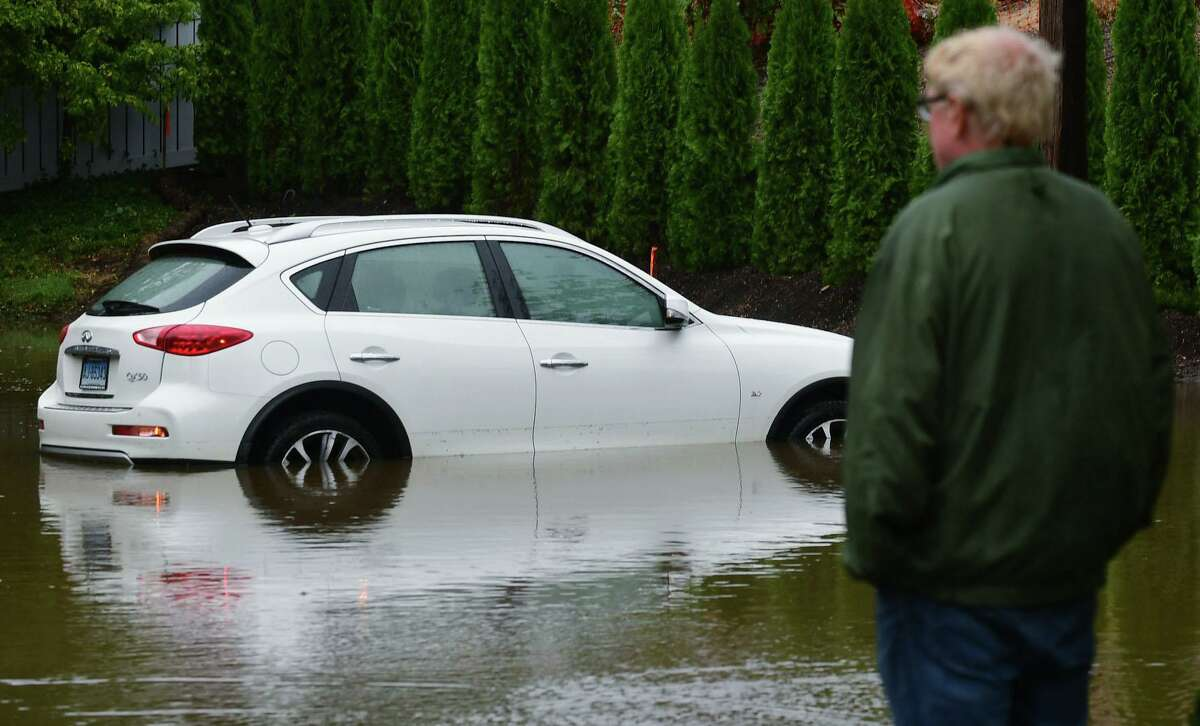 An onlooker gazes on flooded automobiles in the parking lot of the condiminiums on Pine Street Thursday, October 3, 2019, following a water mainn break on Pine Street Extension in Norwalk, Conn.