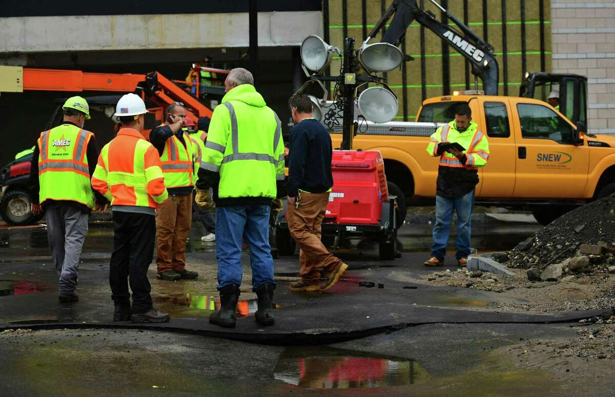 officials from SNEW look over the site of a water main break on Pine Street Extension Thursday, October 3, 2019, which flooded Pine Street Condominiums in Norwalk, Conn.