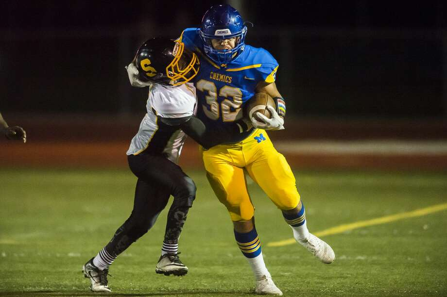 Midland High's Drew Johnson tries to break a tackle during a game against Saginaw High earlier this season. Photo: Daily News File Photo
