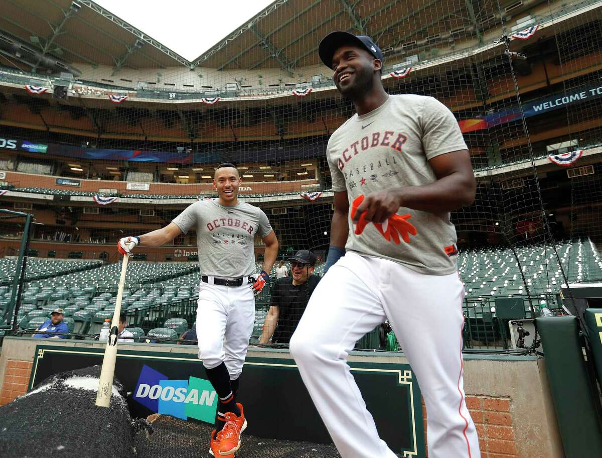Houston Astros Carlos Correa, and Yordan Alvarez stand in the shade, as the roof was left open during batting practice as the Astros prepare for Game 1 of an MLB baseball ALDS playoff game at Minute Maid Park Thursday, Oct. 3, 2019, in Houston .