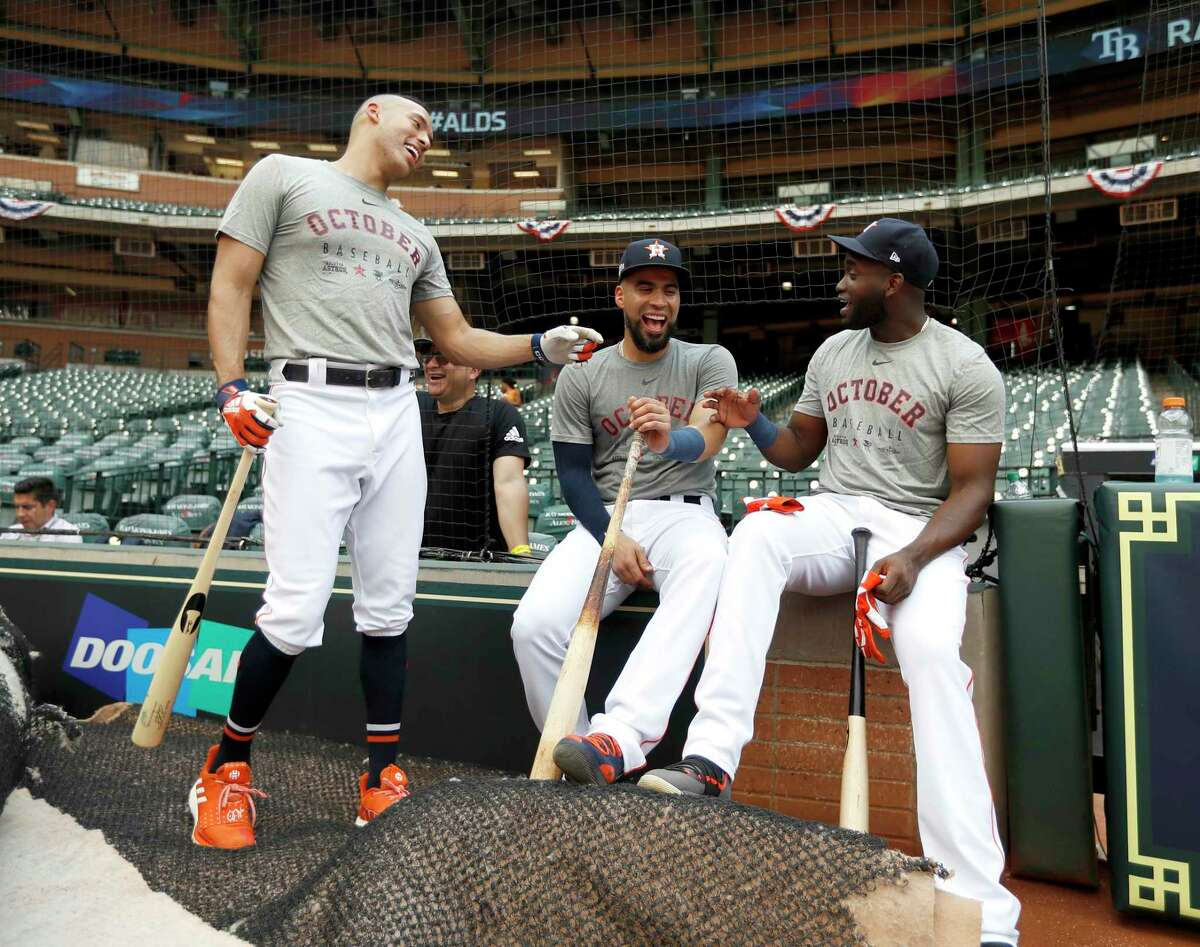 Houston Astros Carlos Correa, Robinson Chirinos, center, and Yordan Alvarez laugh in the shade as the roof was left open during batting practice as the Astros prepare for Game 1 of an MLB baseball ALDS playoff game at Minute Maid Park Thursday, Oct. 3, 2019, in Houston .