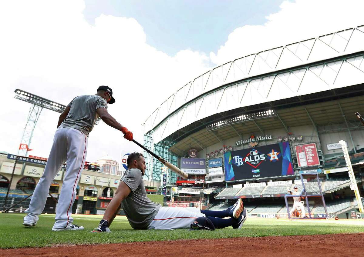 Houston Astros left fielder Michael Brantley puts his bat on George Springer who was sitting in the shade, as the roof was left open during batting practice as the Astros prepare for Game 1 of an MLB baseball ALDS playoff game at Minute Maid Park Thursday, Oct. 3, 2019, in Houston .