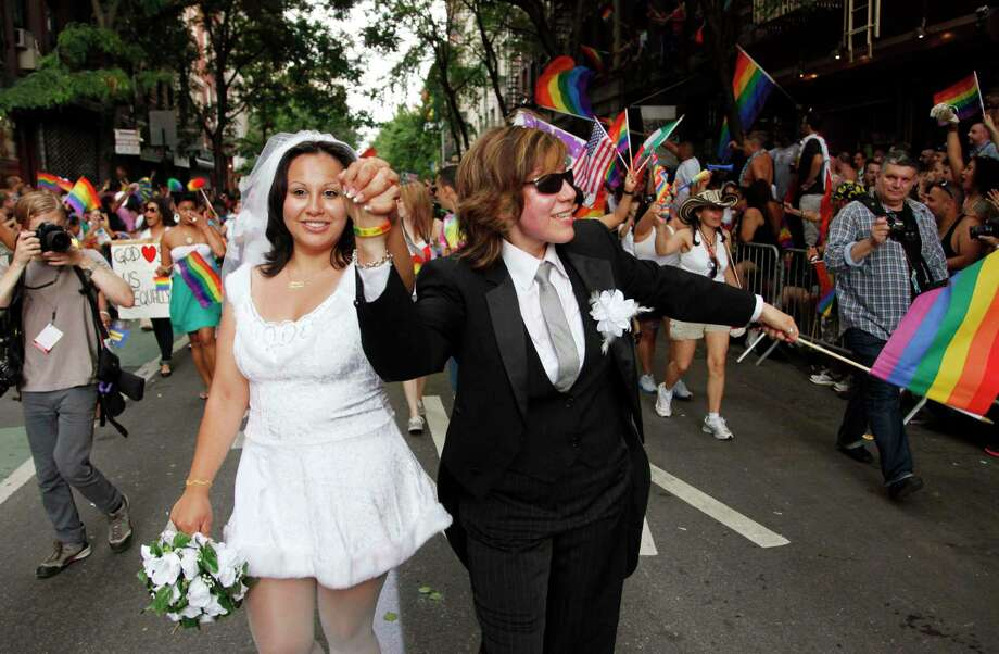 Paola Perez, left, and her partner Linda Collazo march in the annual Gay Pride parade in Greenwich Village June 26, 2011, in New York. Photo: AP / AP