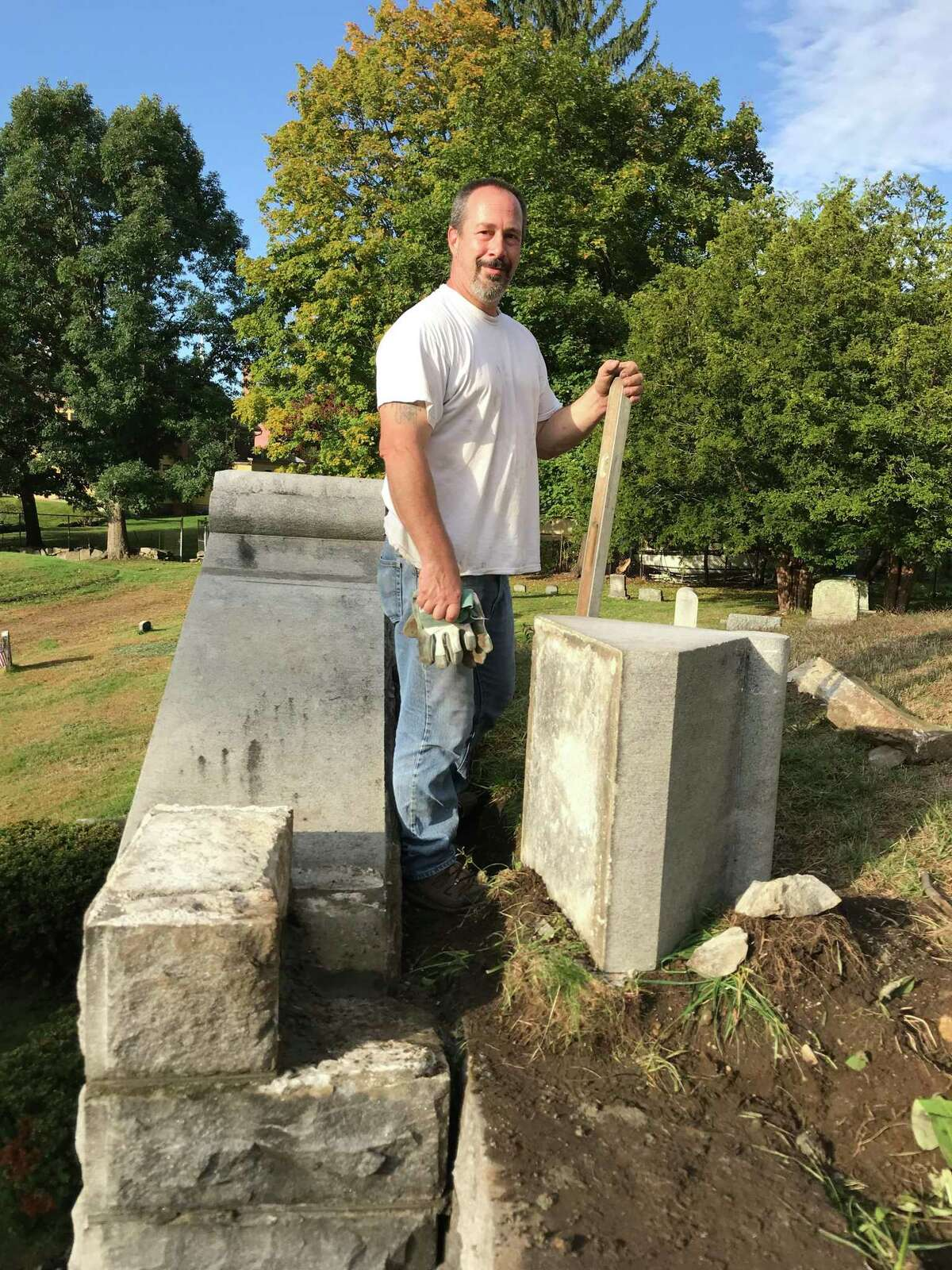 Mason Mike Angelicola works on a granite wall at Center Cemetery in Torrington Tuesday.