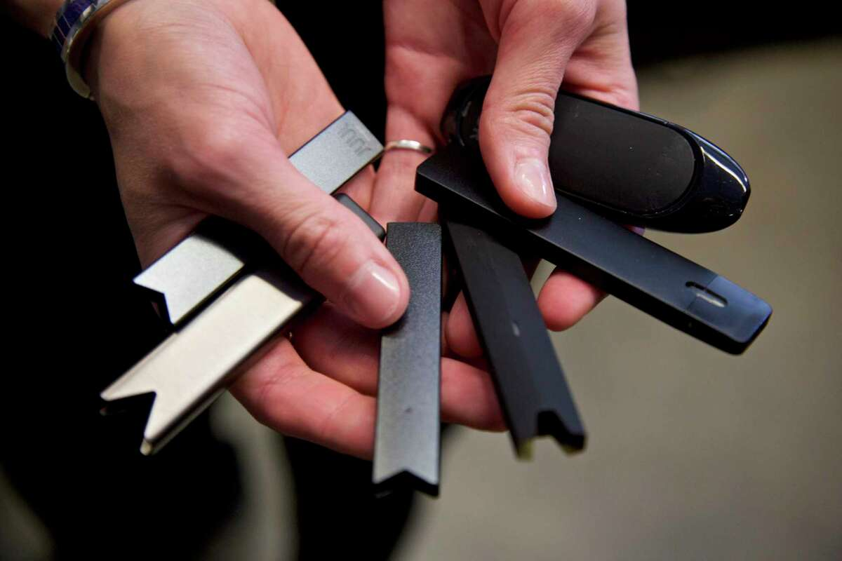 FILE - In this April 16, 2019, file photo, a researcher holds vape pens in a lab at Portland State University in in Portland, Ore. As of October 2019, experts who examined lung tissue from 17 patients say lung damage reported in people who use e-cigarettes and other vaping devices looks like chemical burns similar to what you'd see in people exposed to poisonous gases. (AP Photo/Craig Mitchelldyer, File)