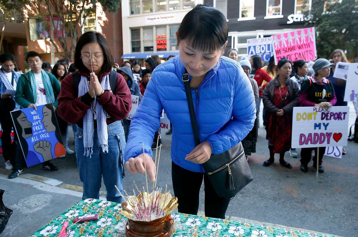 In this file photo from Oct. 3, 2019, Poly Poang lights incense at a demonstration in front of Immigration and Customs Enforcement offices in San Francisco, to protest a sixth round of immigration raids targeting Cambodian refugees. President Trump has invited state and local governments to reject refugee resettlements, but found few takers so far.