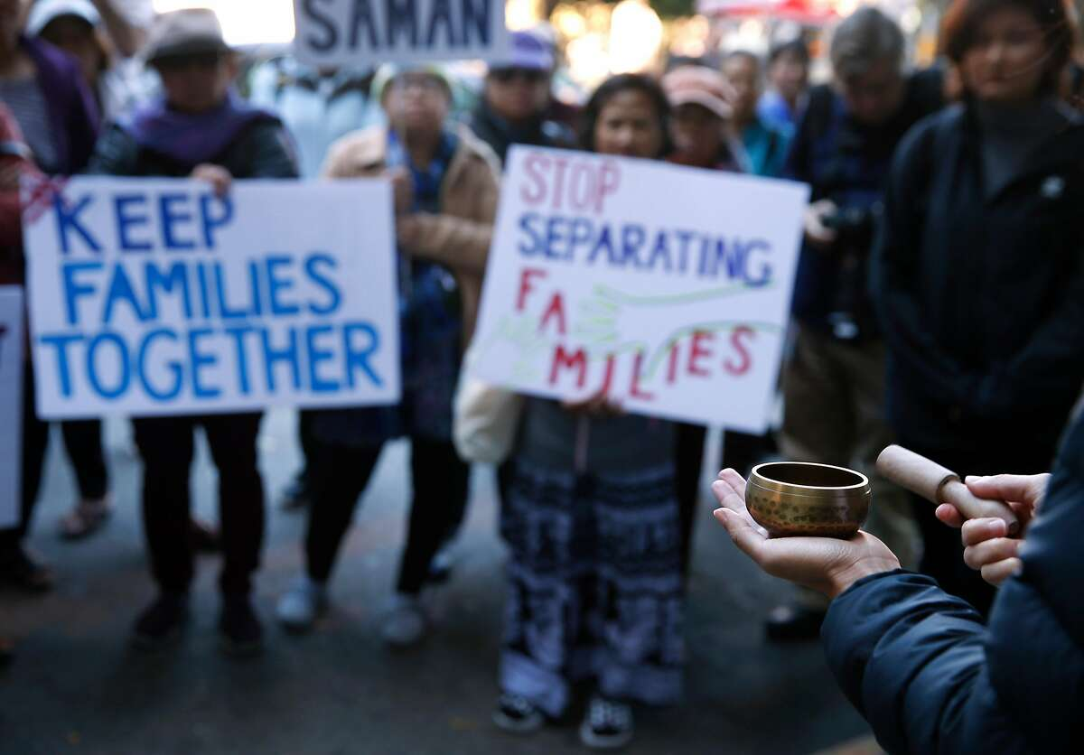 Sarah Lee rings a bell 37 times for each of the Cambodian refugees detained nationwide in a sixth round immigration raids, during a demonstration in front of Immigration and Customs Enforcement offices on Sansome Street in San Francisco, Calif. on Thursday, Oct. 3, 2019.