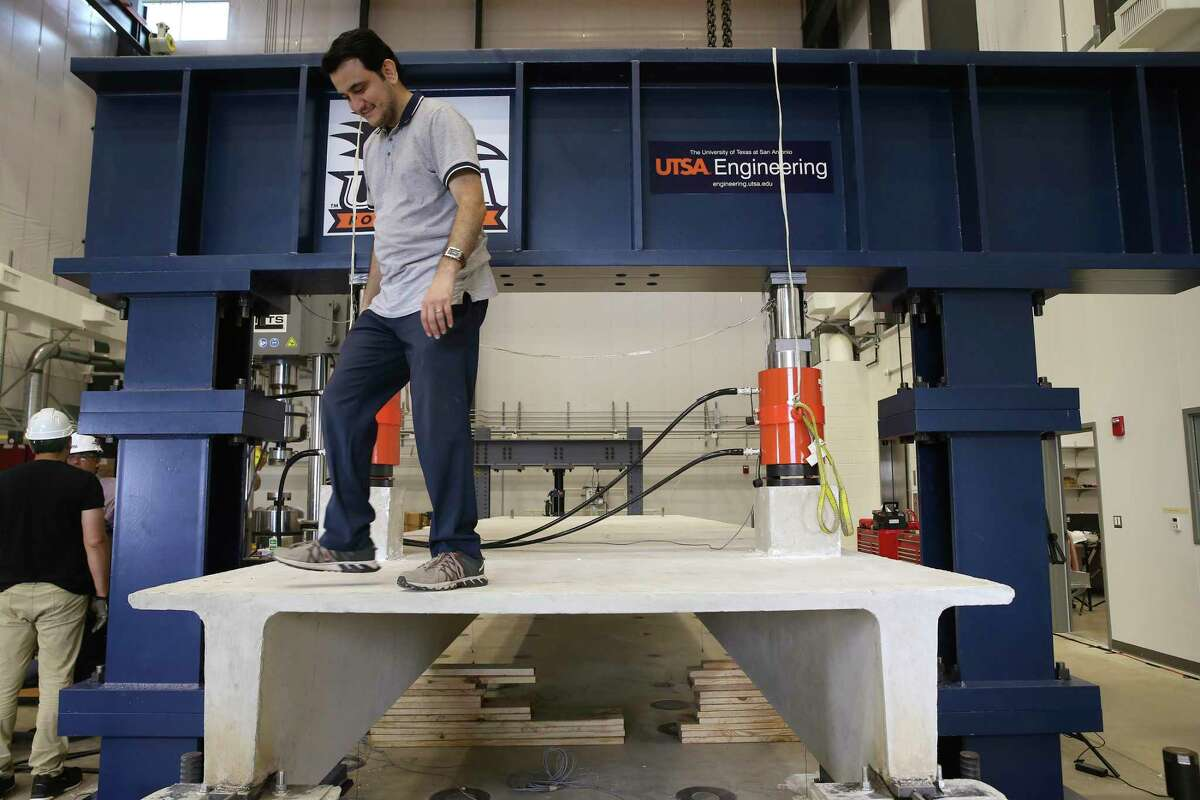 Nader Zad, a doctoral student, checks on equipment used for a live test demonstration at the Large-Scale Testing Lab on Thursday. Pressure was exerted on a concrete girder to the point of fracturing it during the demonstration. The University of Texas at San Antonio inaugurated the facility during a morning ceremony.