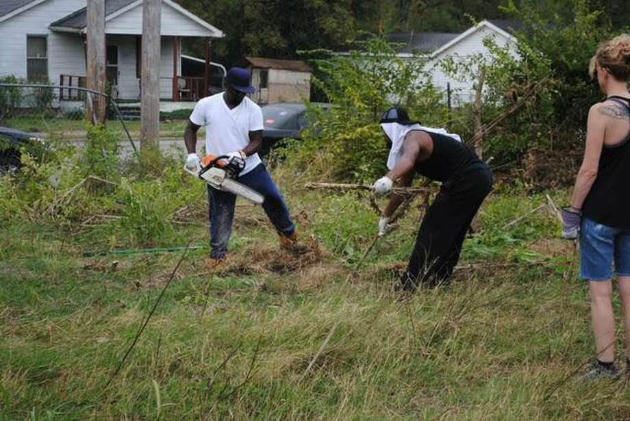 SIUE students and Washington Park residents spend the day cleaning a vacant lot in preparation of creating a community garden.