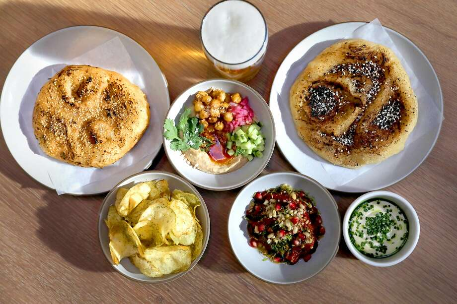Party Bread (top left and right) with Early Girl Tomato curry (bottom middle) and Sichuan Hummus (top middle) with Park beer by Fort Point Beer Co. seen on Tuesday, Oct. 1, 2019, in San Francisco, Calif.  Fort Point Beer Co., San Francisco's largest independent brewery, opens a 3,000-square-foot beer hall on Oct. 7. Photo: Liz Hafalia, The Chronicle