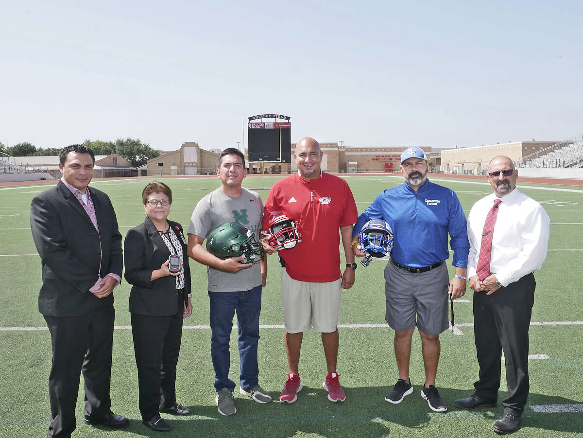 Laredo ISD Athletics Department Director Sylvia barrera and her assistants Luis Escamilla, left and Tommy Ramirez, right, are photographed with Antonio Villalon, head football coach at Nixon, David Charles, head football coach at Martin and Carlo Hein, head football coach at Cigarroa, as they show the Riddell Smart Helmet technology aquired by LISD for football programs in the district.