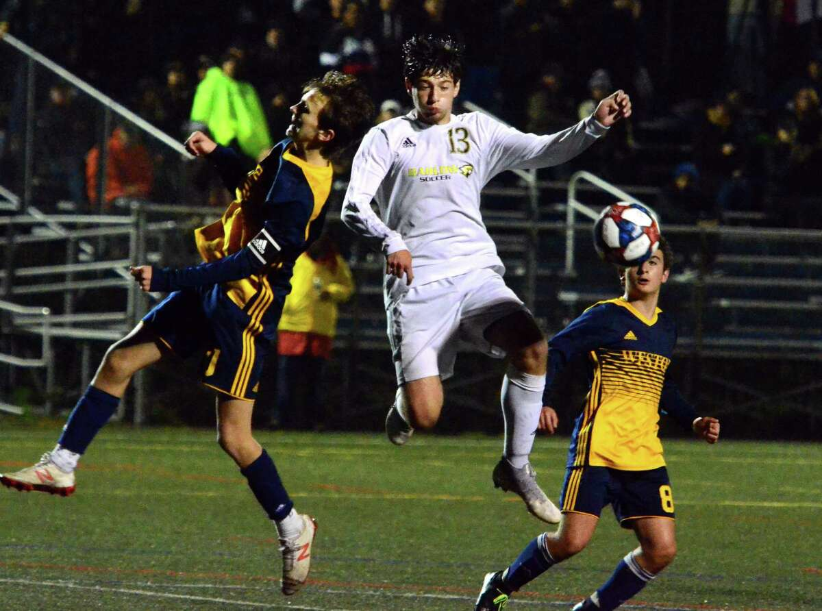 Weston's Jack Fellowes, left, and Joel Barlow's Julio Calish head the ball during boys soccer action in Weston, Conn., on Thursday Oct. 3, 2019.
