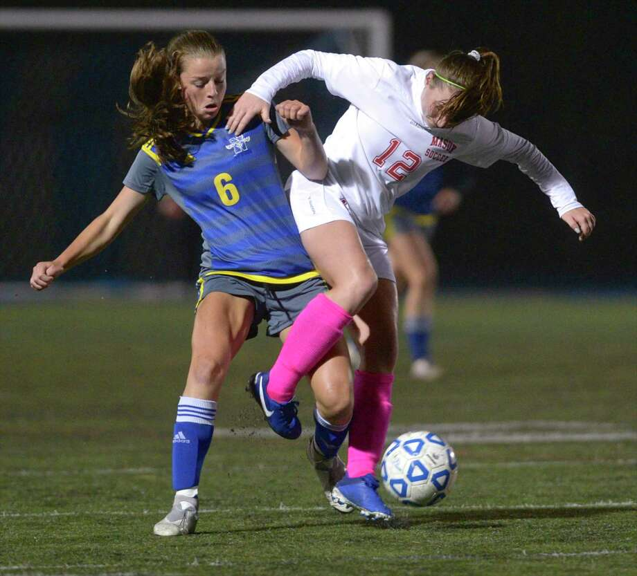 Newtown's Karsen Pirone (6) and Masuk's Emma French (12) fight for the ball in the girls soccer game between Masuk and Newtown high schools. Thursday night, October 3, 2019,at Newtown High School, Newtown, Conn. Photo: H John Voorhees III / Hearst Connecticut Media / The News-Times