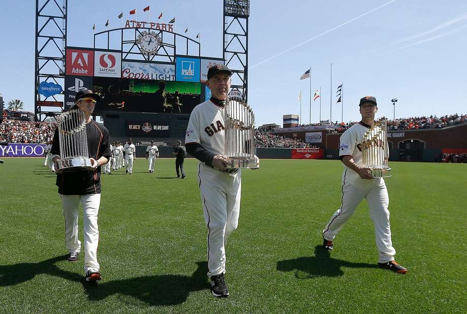 From left, pitcher Tim Lincecum, manager Bruce Bochy and catcher Buster Posey carry the Giants' World Series trophies from the 2010, 2012 and 2014 seasons before a game against the Colorado Rockies in San Francisco, April 13, 2015. Photo: Jeff Chiu / Associated Press