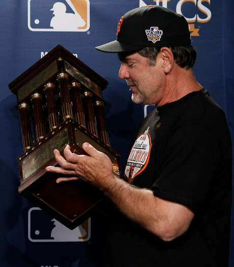 San Francisco Giants manager Bruce Bochy looks at the winning trophy after Game 6 of baseball's National League Championship Series against the Philadelphia Phillies Saturday, Oct. 23, 2010, in Philadelphia. The Giants won 3-2 to win the series and advance to the World Series against the Texas Rangers. (AP Photo/Matt Slocum) Photo: Matt Slocum / AP