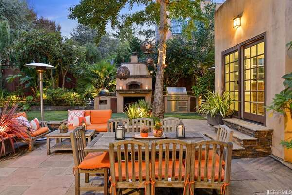 The incredible outdoor space has a built-in kitchen with wood-burning pizza oven, sports court, sunken patio and living roof.