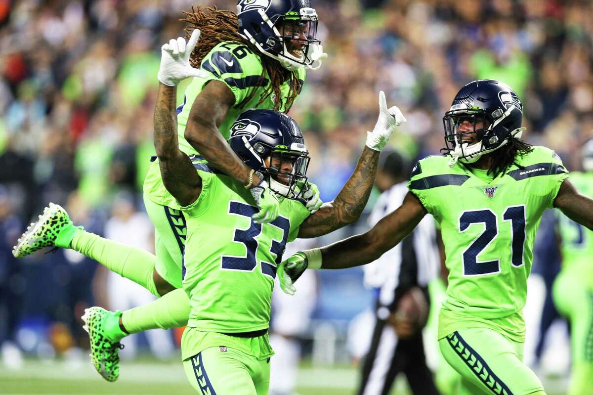 Seattle Seahawks cornerback Shaquill Griffin (26), cornerback Tre Flowers (21) and free safety Tedric Thompson (33) celebrate Thompson's critical interception in the fourth quarter of Seattle's game against the LA Rams, Thursday, Oct. 3, 2019.
