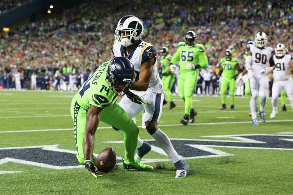 Guarded by Los Angeles Rams cornerback Marcus Peters (22), Seattle Seahawks wide receiver D.K. Metcalf (14) bobbles and drops a catch in the end zone in the fourth quarter of Seattle's game against the LA Rams, Thursday, Oct. 3, 2019.