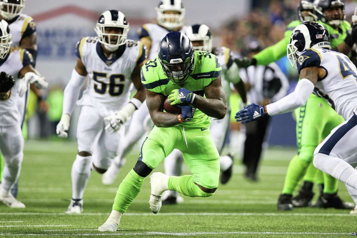 Seattle Seahawks running back Chris Carson (32) finds a hole in the fourth quarter of Seattle's game against the LA Rams, Thursday, Oct. 3, 2019.