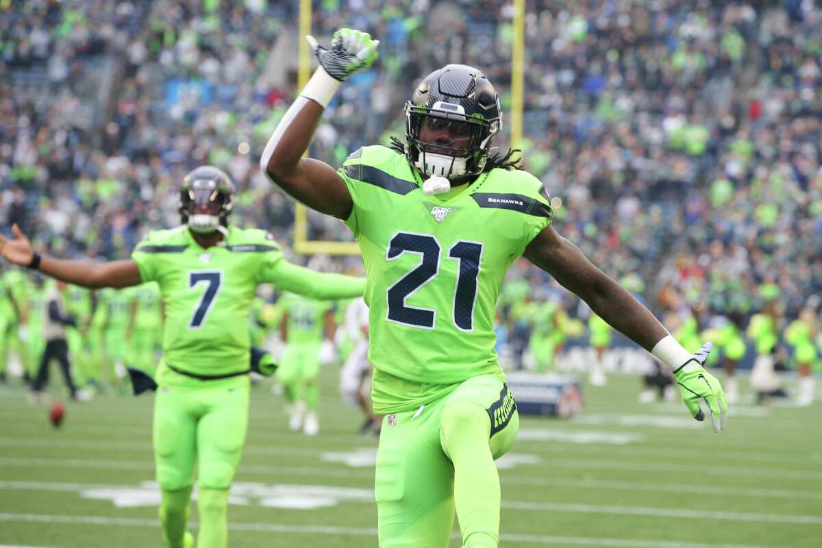 Seattle Seahawks cornerback Tre Flowers (21) and backup quarterback Geno Smith (7) celebrate before the start of Seattle's game against the LA Rams, Thursday, Oct. 3, 2019.